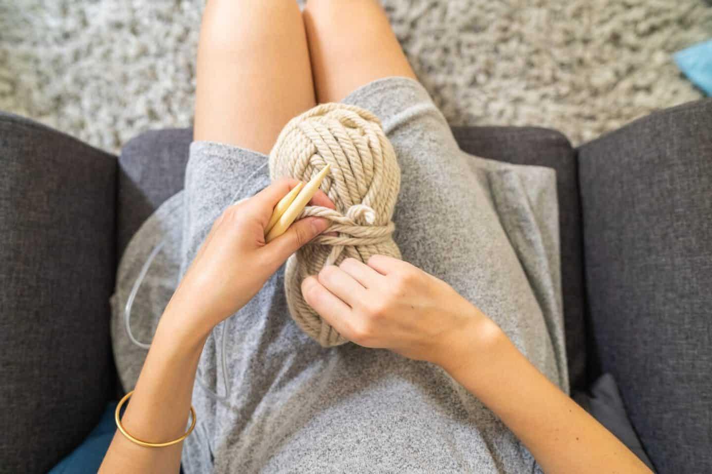 Woman wearing grey dress sitting on a sofa holding a beige yarn