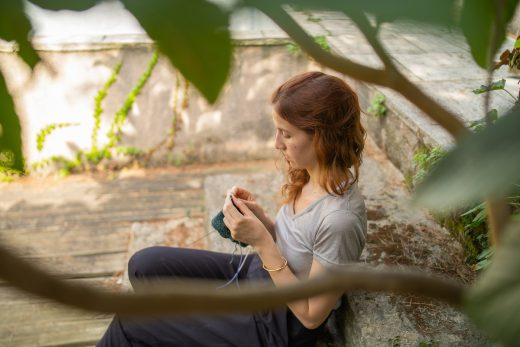 Woman knitting and sitting near concrete bench during daytime photo