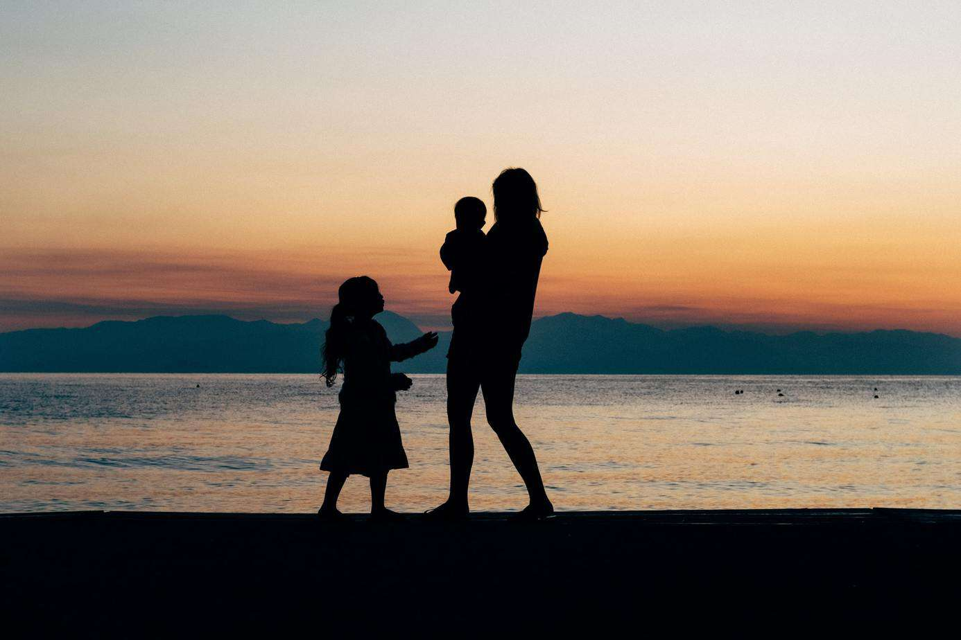 A family of three. Brother, sister and mother, stroll on the beach in Greece at sunrise.