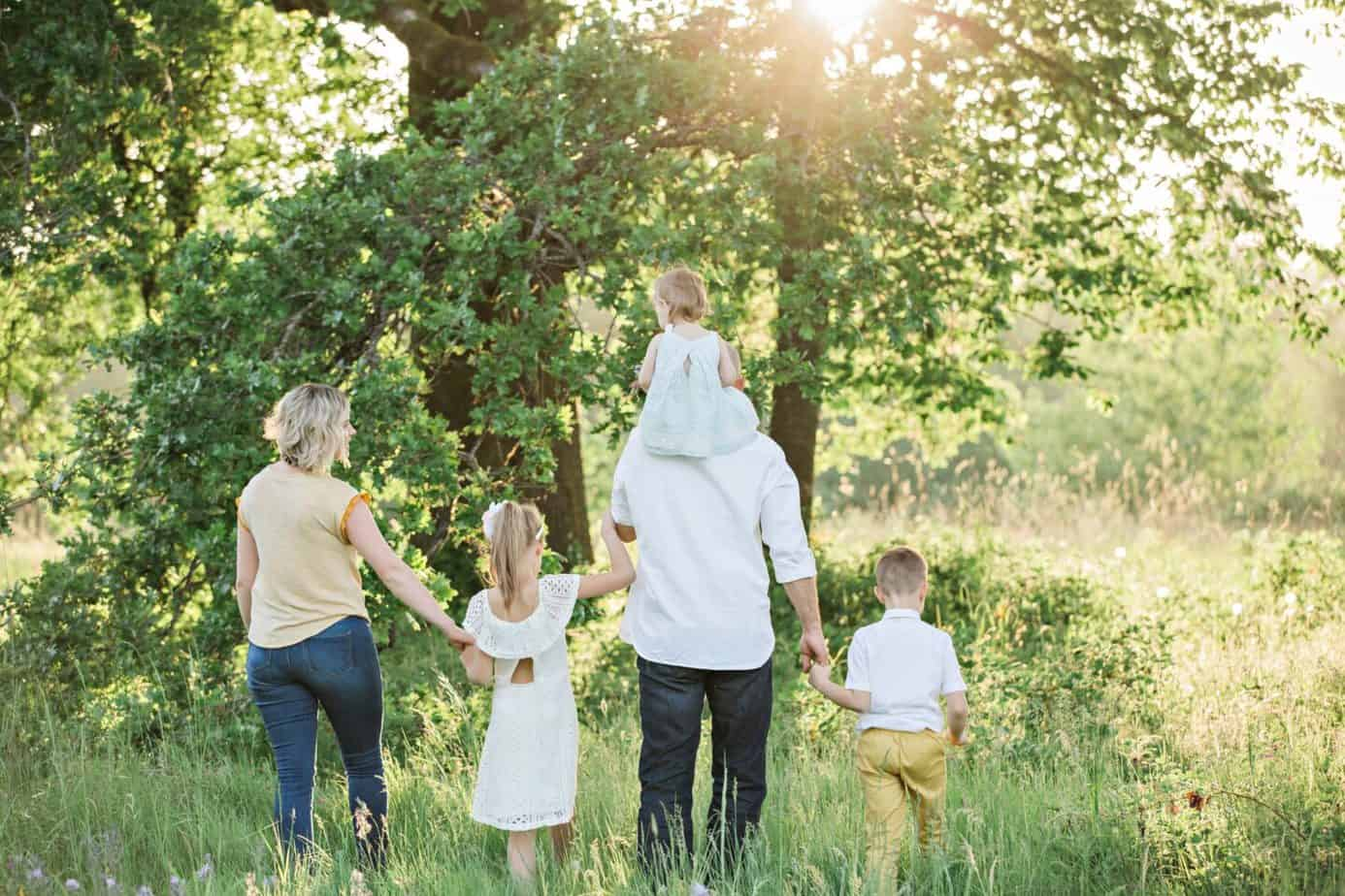 family of five walking towards tree